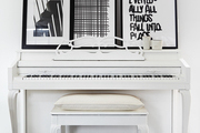The family piano was given a fresh coat of milky-white paint. Black-and-white prints by Therese Sennerholt add energy while casually propped against the wall.