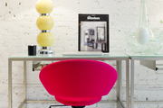 A magenta rolling chair next to a glass desk and table lamp