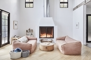 A living room with a fireplace and a pair of pink sofas.