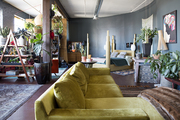An eclectic living space with a chartreuse couch and blue walls.