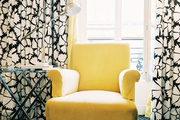 Checkered carpeting and a yellow armchair against floral-patterned curtains