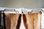 A fur throw pillow layered in front of a pair of bordered shams