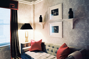 A living space with patterned wallpaper and a tufted couch with red throw pillows