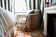 Striped curtains and a slipcovered armchair paired with a patterned rug