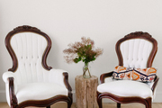 A pair of white settees with a wooden side table.