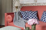 Throw pillows and blanket atop pink couch.