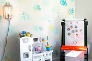 Colorful designs surround a black-floored activity room.