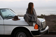 A young woman sits atop the hood of a vintage Mercedes Benz.