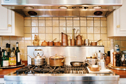 A stainless-steel range topped with a collection of copper cookware