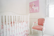 A nursery with a pink upholstered chair and a white crib