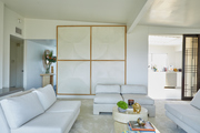 An all-white living room with wall panels.