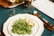 A salad course on a table with horn flatware and a blue velvet tablecloth