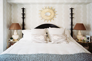 A black four-poster bed dressed with neutral linens and a gray-blue throw