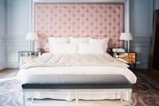 A tufted headboard with a pair of mirrored bedside tables