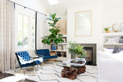 A contemporary living room with blue chairs and a white sofa.
