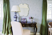 Green curtains and blue floral wallpaper paired with a black vanity