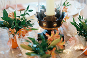 A dining table decorated with flowers, a hurricane lamp, and oranges
