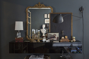 A tablescape in a living room painted in a moody hue