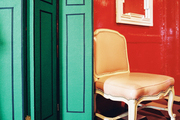 A green folding screen in a room with red lacquered walls and a geometric-patterned floor