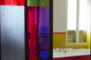 Beyond a stained-glass sliding door, a red-painted clawfoot tub in a Paris bathroom