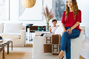 Designer Jenni Kayne and her son, Tanner, in her family living space with two white sofas, a pendant light, and modern artworks