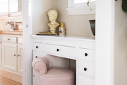 A pink vanity stool in a powder room