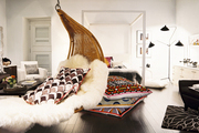 A hanging rattan chair with patterned pillows and sheepskin throws