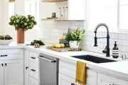 A white kitchen with marble counter tops and black accent pieces.