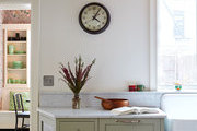 An old clock hangs in an updated kitchen