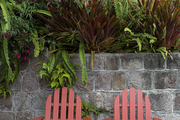 A pair of Adirondack chairs on a stone patio backed by exotic foliage