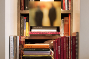A collection of books on the shelves in the corner of a living room