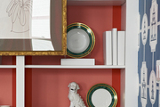 A built-in bookcase filled with malachite dishes, foo dogs, and books covered in white paper,  designed by BHDM.