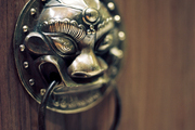 A brass door knocker used as cabinet hardware in a powder room