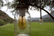 Mason-jar lamps suspended from tree branches