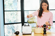 Katie Lee at a wooden table preparing minted green soup