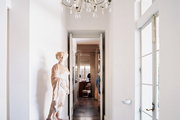 A chandelier and a terra-cotta statue in a white-walled entryway