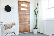 The wooden front door to this rental is adjacent to a cactus and mod chair.