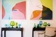 Colorful art above a pair of carved-wood tables