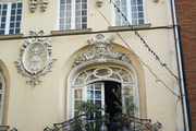 French doors opening onto a balcony decorated with potted plants