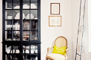 A black china cabinet, a French-style chair, and a ladder draped with table linens