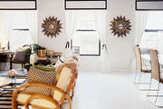 Gold starburst mirrors framed by white curtains