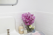 A vase of flowers and striped hand towels in an all-white bathroom