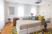 A transitional daybed on a yellow and gray rug.