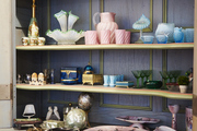 Colorful array of glassware and decor on a Victorian bookshelf.