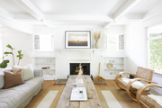 A white living area with wall pieces and neutral furniture tones.