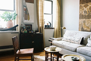 A pair of tray tables set atop a hide rug beside a white couch