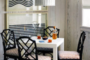 A white Parsons table surrounded by painted rattan chairs