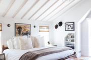 A striped rug and neutral bed linens in a room with a pitched ceiling