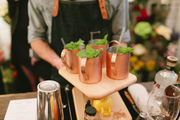 Four cocktails being served on a wooden board.