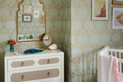 Patterned wallpaper and traditional furniture in babies room.